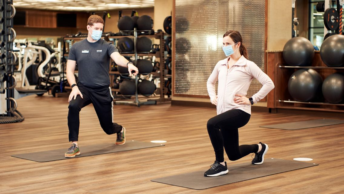 a trainer works with a member while wearing masks