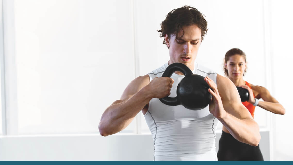 A man and woman lifting kettlebells