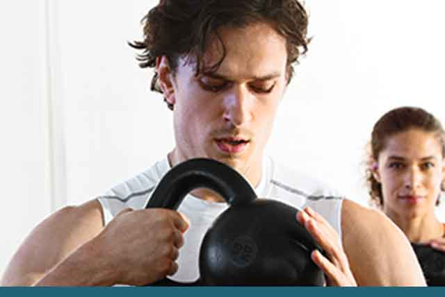 Man holds kettlebell near his chest