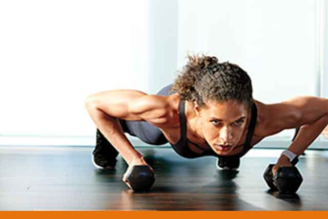 A woman in plank position with dumbbells