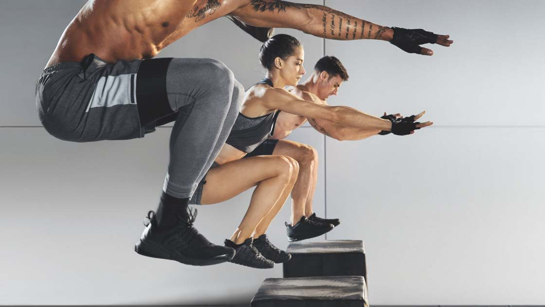 Men and women jumping in synch during a group fitness class