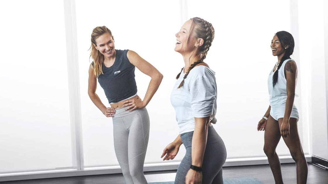 Three young women laughing during a group fitness class