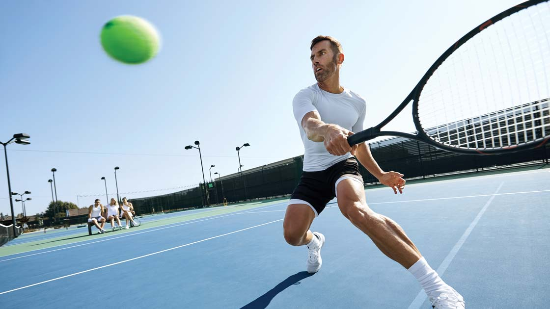 A man hitting a tennis ball with a tennis racquet