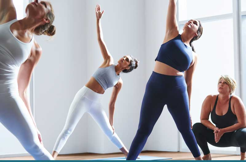 Four people holding yoga poses in a yoga studio at Life Time